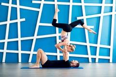 Paare übendes acro Yoga in einem Studio Acro-Yogakonzept Paaryogaklasse Lizenzfreie Stockfotografie