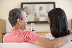 Paare in überwachendem Fernsehen des Wohnzimmers Lizenzfreies Stockfoto