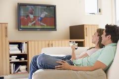 Paare in überwachendem Fernsehen des Wohnzimmers Lizenzfreie Stockfotografie