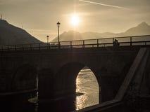 Paare auf Brücke während des Sonnenuntergangs Stockfoto