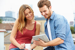 Paare auf Dach-Terrasse unter Verwendung Digital-Tablets Stockfotos