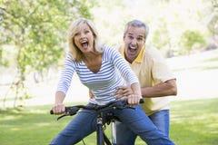 Paare auf dem Fahrrad, das draußen erschrocken lächelt und fungiert Lizenzfreie Stockfotos