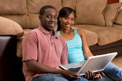 Paare auf dem Fußboden mit einem Laptop-Horizontalen Lizenzfreies Stockbild