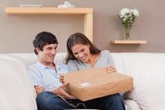 Paare auf dem Sofaöffnungspaket lizenzfreie stockbilder