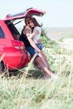 Paare auf dem Strand auf einem roten Auto Stockbilder