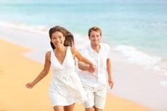 Paare auf dem Strand, der das Spaßlachen habend läuft Stockfotografie