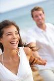 Paare auf dem Strand, der Spaßlebensstil habend lacht Lizenzfreies Stockbild