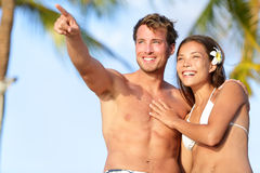 Paare auf dem Strand glücklich in der Badebekleidung, Mannzeigen Lizenzfreies Stockfoto