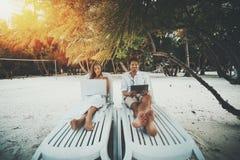 Paare auf dem Strand mit ihren Geräten Lizenzfreies Stockbild