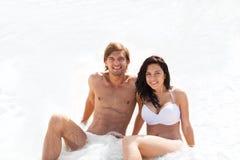 Paare auf dem Strand, sitzend im Wasserwellen-Schaummeer Stockfotografie