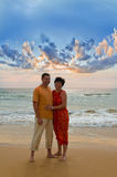 Paare auf dem Strand am Sonnenuntergang Stockfoto