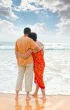 Paare auf dem Strand am Sonnenuntergang Lizenzfreie Stockfotos