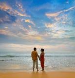Paare auf dem Strand am Sonnenuntergang Stockbilder