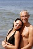Paare auf dem Strandumarmen Stockfotografie