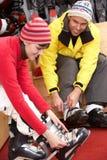 Paare auf dem Versuchen auf Skistiefeln im Miete-System Stockbild