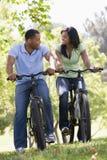 Paare auf den draußen lächelnden Fahrrädern Lizenzfreie Stockfotografie