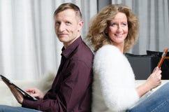 Paare auf der Couch, die Kamera untersucht lizenzfreie stockfotos
