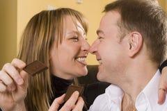 Paare auf der Couch, die Schokolade isst Stockfoto