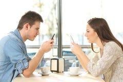 Paare auf der Linie besessen gewesen mit intelligenten Telefonen Stockfotos