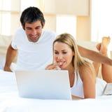 Paare auf einem Bett Stockfotos
