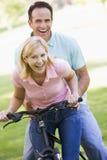 Paare auf einem draußen lächelnden Fahrrad Stockbild