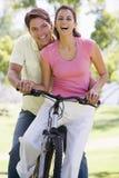 Paare auf einem draußen lächelnden Fahrrad Stockfoto