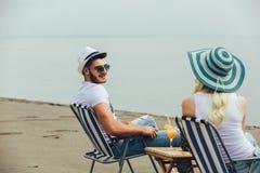 Paare auf einem Klappstuhl, der auf dem Strand sich entspannt stockbilder