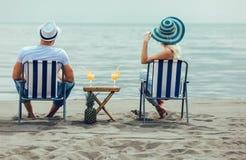 Paare auf einem Klappstuhl, der auf dem Strand sich entspannt lizenzfreie stockfotografie