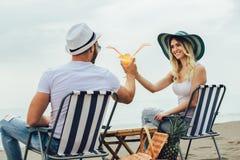Paare auf einem Klappstuhl, der auf dem Strand sich entspannt stockbild