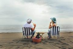 Paare auf einem Klappstuhl, der auf dem Strand sich entspannt lizenzfreies stockfoto