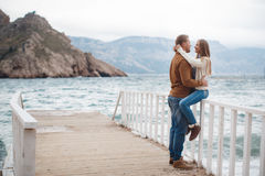 Paare auf hölzernem Pier nahe dem Meer im Herbst Stockfotos