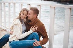 Paare auf hölzernem Pier nahe dem Meer im Herbst Stockbild