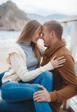 Paare auf hölzernem Pier nahe dem Meer im Herbst Lizenzfreie Stockbilder