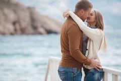 Paare auf hölzernem Pier nahe dem Meer im Herbst Lizenzfreies Stockfoto