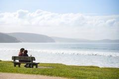 Paare auf Holzbank schauen heraus zum Meer Lizenzfreie Stockfotos