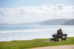 Paare auf Holzbank schauen heraus zum Meer Lizenzfreies Stockfoto