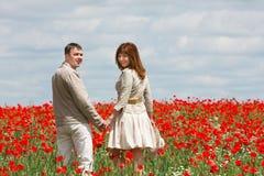 Paare auf rotem Mohnblumefeld lizenzfreie stockbilder
