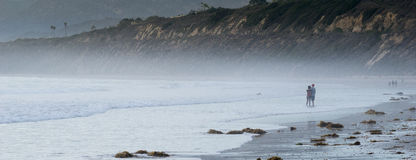 Paare auf schwermütigem Strand Stockfotos