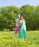 Paare auf Wiese mit gelbem Löwenzahn Stockbilder