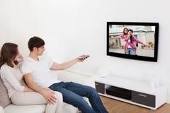 Paare in aufpassendem Fernsehen des Wohnzimmers Lizenzfreies Stockbild