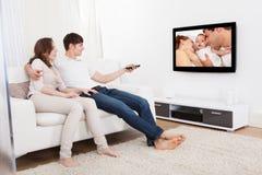 Paare in aufpassendem Fernsehen des Wohnzimmers Lizenzfreie Stockfotos