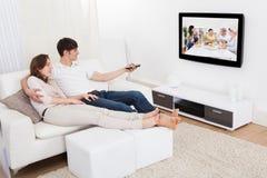 Paare in aufpassendem Fernsehen des Wohnzimmers Stockfoto