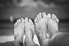 2 Paare Beine auf dem Hintergrund des Ozeans in Schwarzweiss Stockbilder