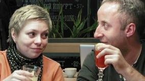 Paare bemannen und Frauengeklirrgläser isst und spricht stock video footage