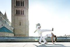 Paare capoeira Ausführende, die ein Treten tun lizenzfreies stockfoto