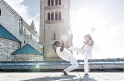 Paare capoeira Ausführende, die ein Treten tun lizenzfreies stockbild