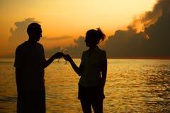 Paare Clinkgläser. Schattenbilder gegen Meer Stockfotografie