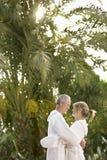 Paare in den Bademäntel, die durch Palmen umarmen Lizenzfreies Stockbild
