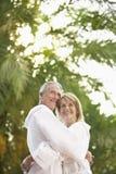 Paare in den Bademäntel, die durch Palmen umarmen Stockfoto