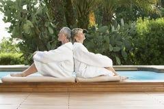 Paare in den Bademäntel, die zurück zu Rückseite durch Pool sitzen Stockfotos
